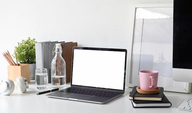 空白の画面のラップトップコンピュータと白い机のオフィスのテーブルの模型の白いポスターでロフトのワークスペース