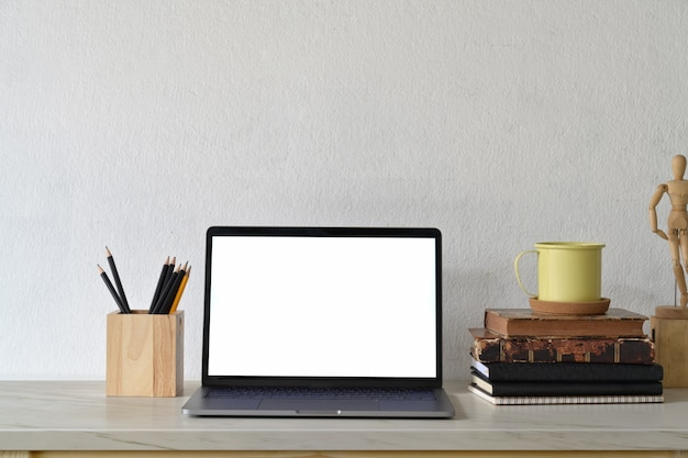 Loft workspace with blank white screen laptop and creative gadget.