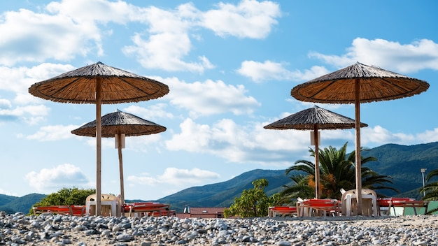 Log beach umbrellas with mountains on the background in asprovalta,greece