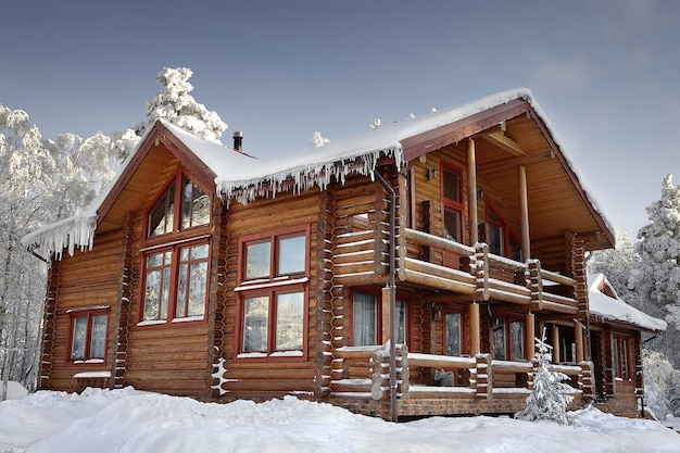 대형 창문, 발코니 및 현관, 현대적인 주택 디자인, 눈 덮인 겨울이있는 통나무 집.
