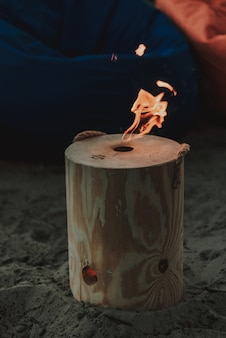 Log with fire hole standing on beach.