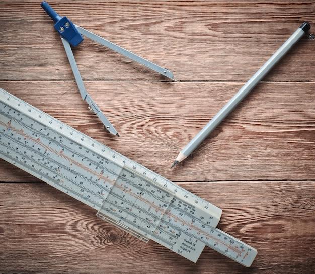 Логарифмическая линейка, компасы, карандаш на деревянном столе. канцтовары для инженеров и студентов.