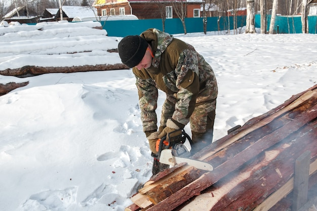 Logger saws a tree  fores winter, in russia for firewood.
