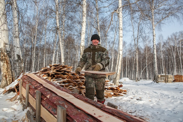 A logger saws a tree in the forest in winter, russia for firewood.