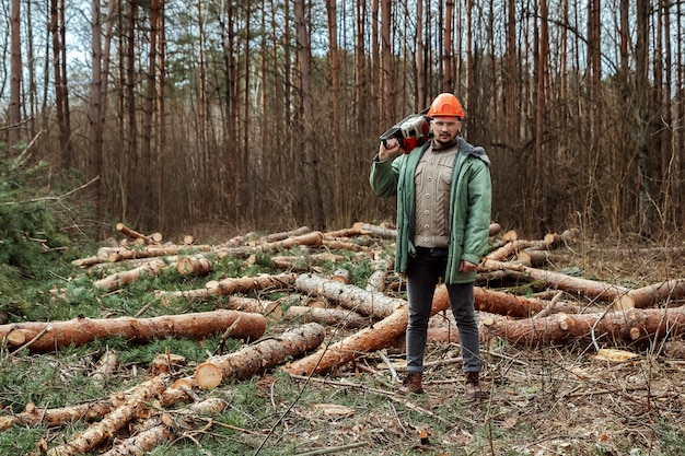 Logging, worker in a protective suit with a chainsaw