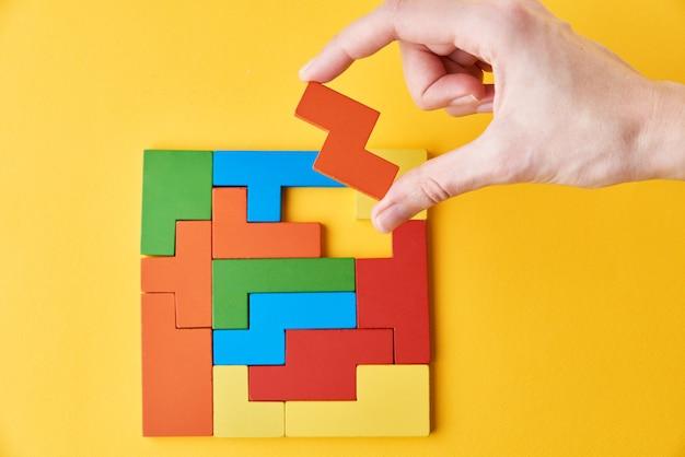 논리적 사고와 마무리 작업 개념. 여자 손 마지막 누락 된 나무 블록을 추가하여 퍼즐을 완료