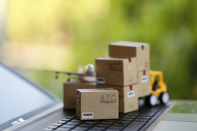 Концепция логистики и перевозки груза: автопогрузчик двигает бумажную коробку на клавиатуре тетради в естественной зеленой природе. изображает международную службу доставки или доставки для покупок в интернете.