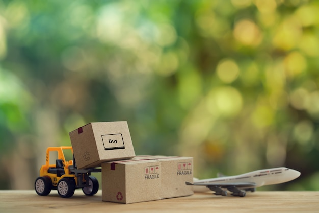 Logistic and cargo freight concept: fork-lift truck moves a pallet with paper boxes, plane.