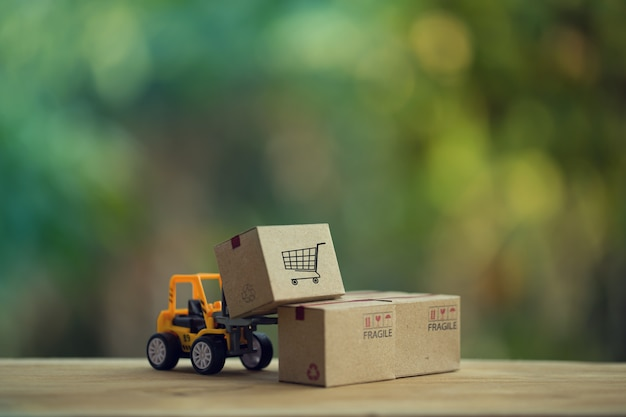 Logistic and cargo freight concept: fork-lift truck moves a pallet with paper boxes.