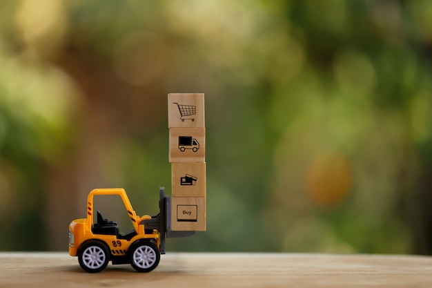 Logistic network distribution and cargo freight concept: mini fork-lift truck moves a pallet with wooden block with icon. depicts delivering goods or products around globe in e-commerce.