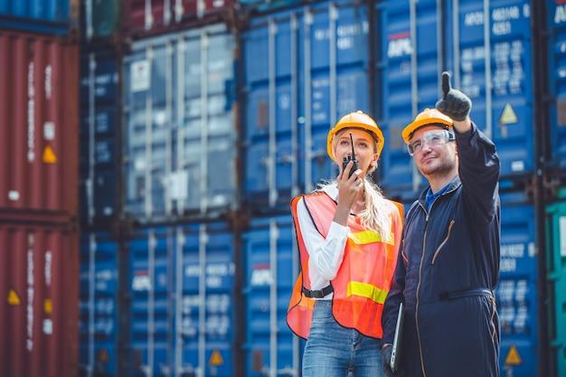 港湾貨物にラジコン積み込みコンテナを備えたロジスティック労働者の男女作業チーム