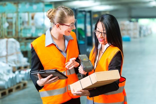 물류-여성 노동자 또는 화주 및 직원 또는 동료가 보호 조끼와 스캐너를 사용하여화물의 바코드를 스캔하고화물 운송 회사의 창고에 서 있습니다.