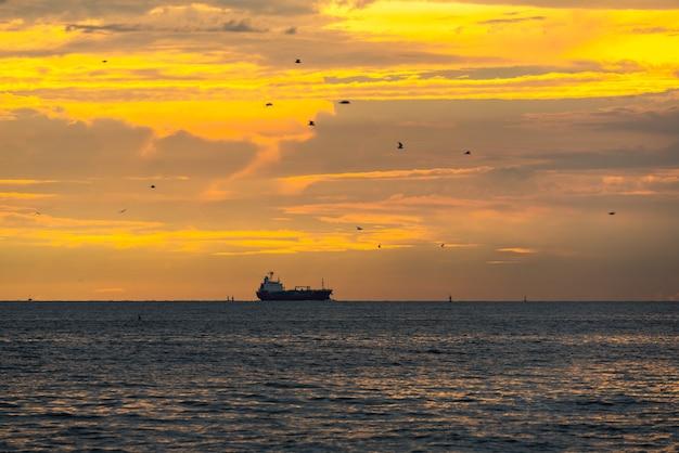 Логистика импорт-экспорт контейнеровоз грузовой корабль в морском порту на закате небо, грузовые перевозки на лодке контейнеровоза