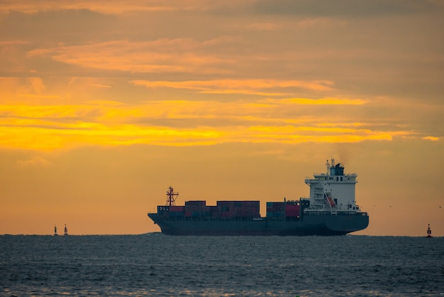 Logistics import export container cargo ship in seaport on sunset sky, freight transportation by container ship boat