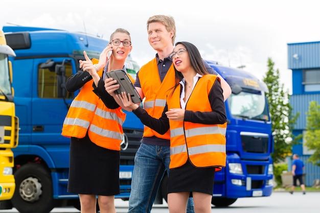 Логистика - гордый водитель или экспедитор и коллеги с планшетным компьютером, перед грузовиками и прицепами, на перевалочном пункте, это хорошая и успешная команда