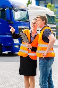 Логистика - гордый водитель или экспедитор и женщина-коллега с планшетным компьютером, перед грузовиками и прицепами, на перевалочном пункте, это хорошая и успешная команда.