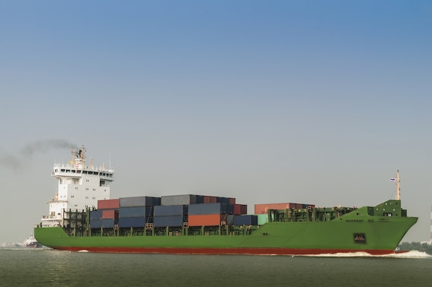 Logistics and transportation container cargo ship with tugboat in the ocean