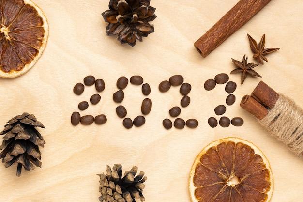 갈색 나무 배경에 커피 콩과 향신료의 로고 2022. 2022년 새해 복 많이 받으세요
