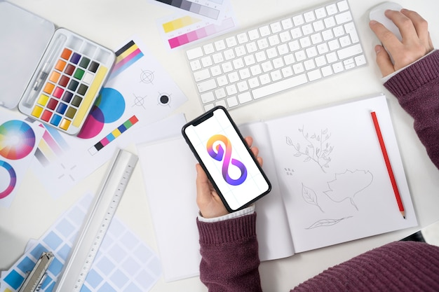 Дизайнер логотипов держит смартфон с крутым логотипом на нем