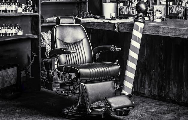 Логотип парикмахерской, символ. стильное винтажное кресло для парикмахера. парикмахер в интерьере парикмахерской. стул парикмахерской. кресло для парикмахерских, салон, парикмахерская для мужчин. полюс парикмахерской. черное и белое.