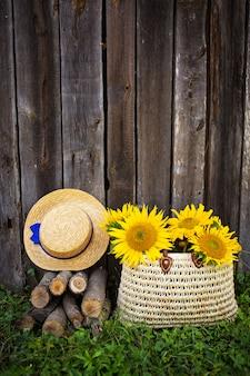 木造住宅の近くに丸太、帽子、ストローバッグに入ったひまわりの花束が立っています。