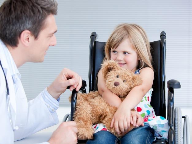 医者でlokking車椅子に座っている少女を笑って