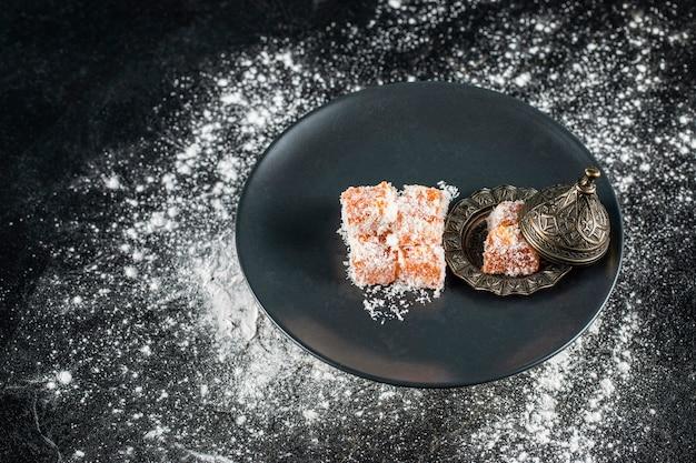 Конфеты lokum в черной тарелке
