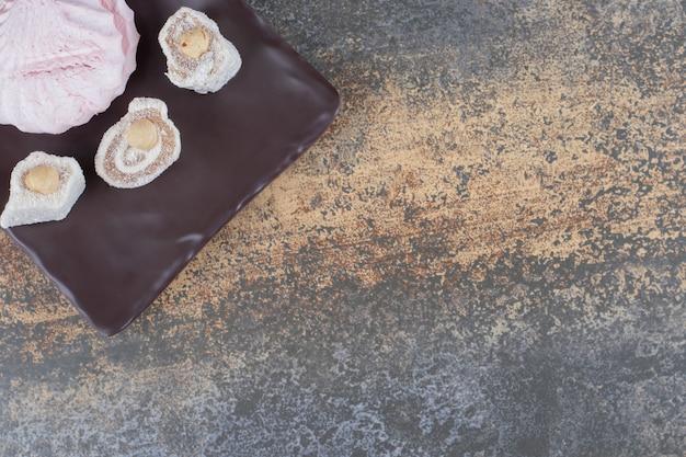 木製の表面の大皿にクッキーの周りのロクム