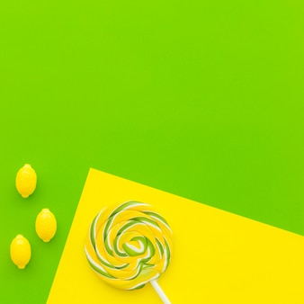 Lollipop and lemon candies on dual yellow and green background