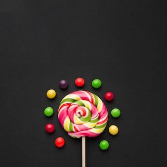 Леденец и конфеты на черном столе