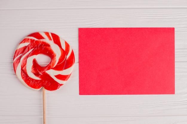 ロリポップキャンディーと白紙のカード。フラットレイの赤い紙シートとスパイラルロリポップ。上面図