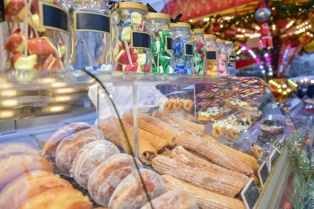 フランスのクリスマスマーケットのカウンターにあるロリポップドーナツとケーキ