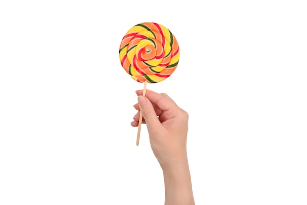 Lollipop in female hand isolated on white  background. space for text or design.