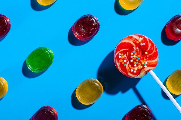 Леденец на палочке среди цветных конфет