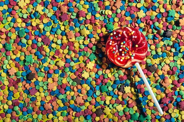 Леденец на палочке среди красочных кондитерских обсыпок