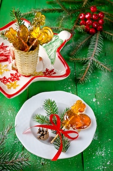 Lollipop in shape of rooster on the stick on christmas table