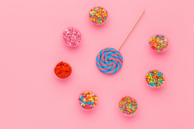 Lollipop and sugar sprinkles in paper bowls on pink background, top view