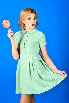 ロリポップ甘い食べ物ピンナップモデルとロリポップを手に面白いレトロなファッションの女の子と夏のドレス