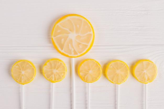 スティックにレモンの形をしたロリポップ。レモンのスライスの形でロリポップのセット。上面図