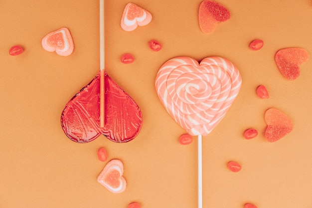 Lollipops, marmalade. gummy candies in the form of hearts on an orange background. valentine's day concept.