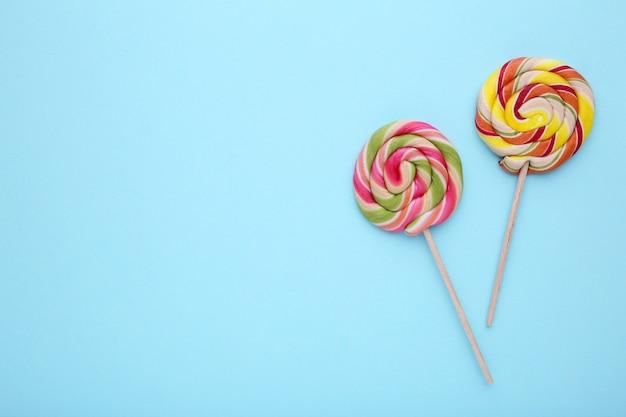 Леденцы на палочке на синем фоне. концепция сладких конфет