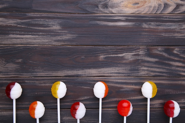 Леденцы на палочке на коричневом фоне. концепция сладких конфет