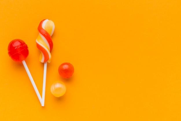 コピースペースを持つオレンジ色のテーブルの上のロリポップ