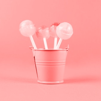 Lollipops in the small painted bucket against coral background