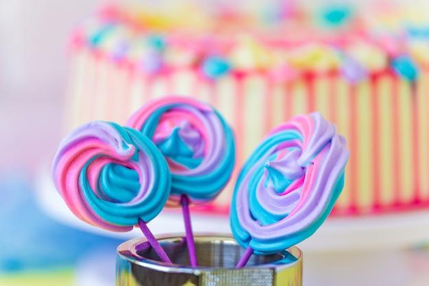 ピンクの背景にロリポップスパイラルフォームキャンディー。面白いコンセプト。紙棒のメレンゲキャンディー。子供のためのお祝いの甘いテーブル。キャンディーバー。背景としてケーキ。