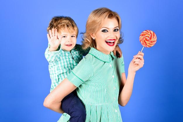 ロリーポップの甘い食べ物のデザートシュガーと幸せな子供を背負ってコンセプトの美しいピンナップモデルを楽しんでいます