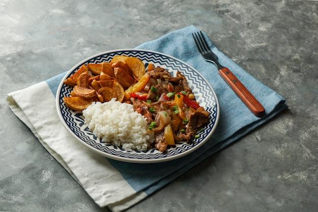 Перуанское блюдо lomo saltado, приготовленное из говяжьей вырезки с красным луком, желтым чили, помидорами, картофелем фри и рисом