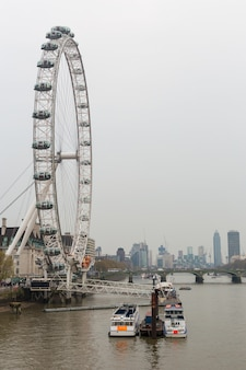London eye with city view and tourist boat.