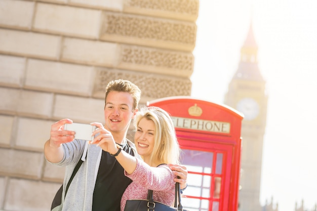 London, happy young couple taking a selfie