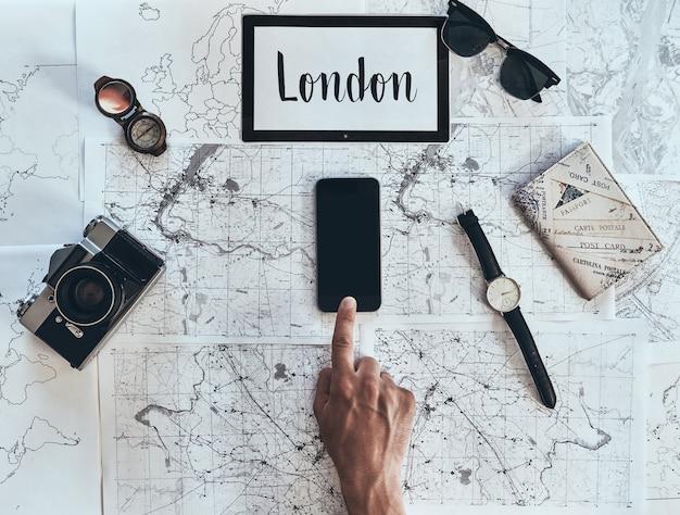 런던은 새로운 목적지입니다. 선글라스와 함께 스마트 폰을 사용하는 남자의 상위 뷰를 닫습니다